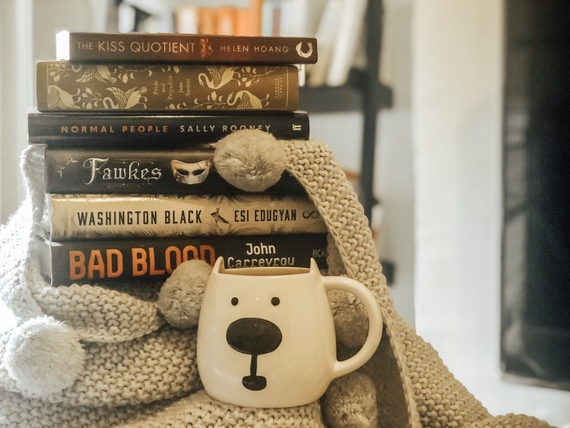 Books stacked in winter scene. The Kiss Quotient by Helen Hoang, Pride and Prejudice by Jane Austen, Normal People by Sally Rooney, Fawkes by Nadine Brandes, Washington Black by Esi Edugyan, Bad Blood by John Carreyrou